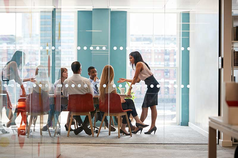 female-boss-stands-leaning-on-table-at-business