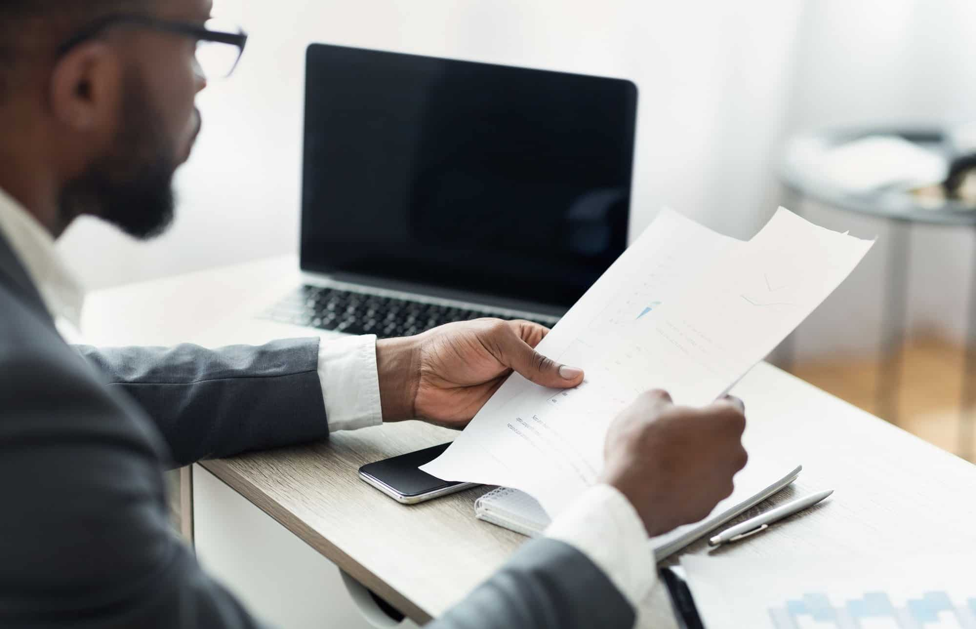 african entrepreneur reading financial reports working in modern office
