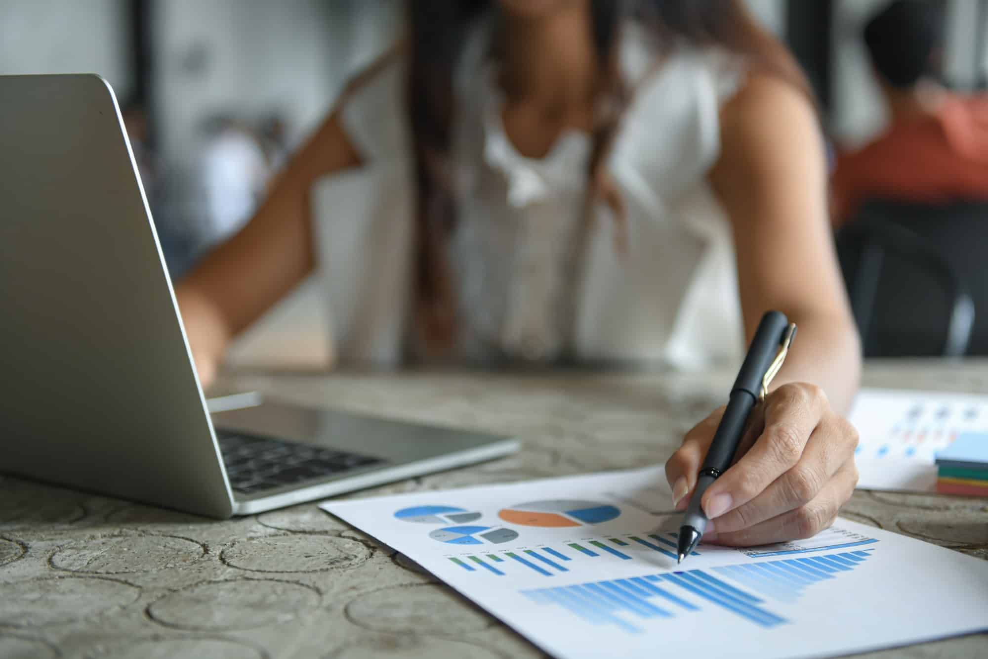 hand of a businesswoman is holding a pen pointing at the graph and using a laptop